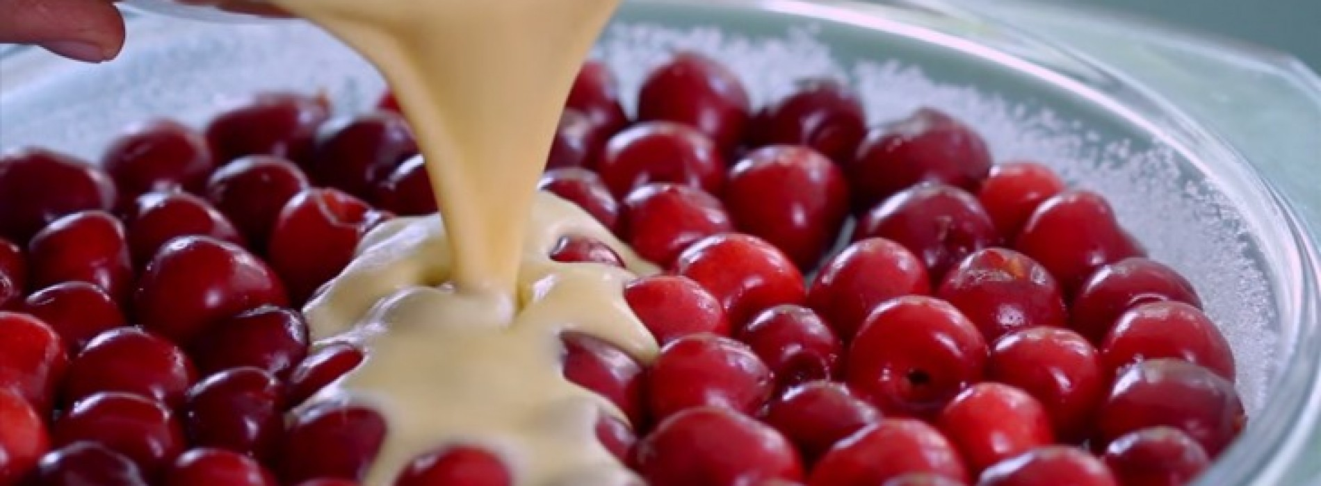 Ze schenkt beslag over een laag verse kersen en creëert hiermee een overheerlijke en onweerstaanbaar dessert!